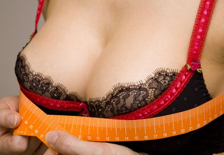 Closeup of a sensual woman measuring her bust size with a tape-measure photo