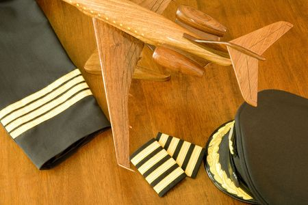 A pilots uniform, cap and a wooden aircraft on a table