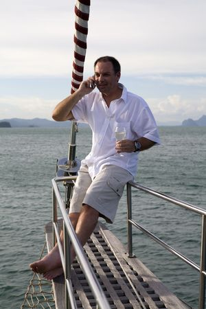 wealthy: Handsome man on deck of yacht with mobile phone and drinking wine Stock Photo