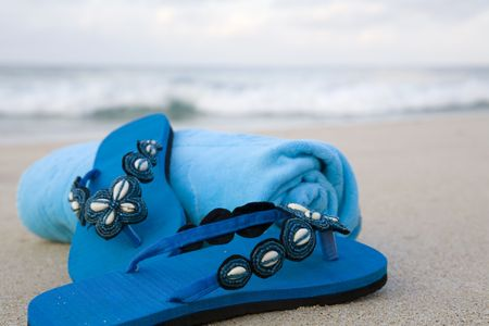 toweling: Turquoise flip flops and towel on a beach Stock Photo