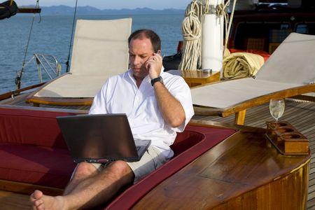 金持ち: 携帯電話やノート パソコンと一緒にヨットのデッキにハンサムな男