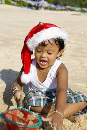 thai boy: Little Thai boy with christmas hat playing on beach