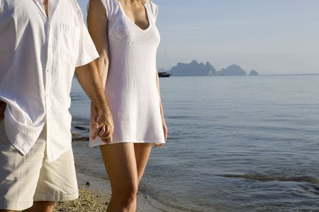 mate married: A couple walking on the beach holding hands