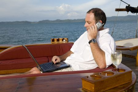 Handsome man on deck of yacht with mobile phone and laptop