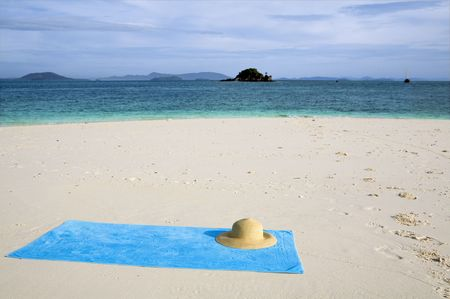 toweling: A turquoise towel and sun hat on a white beach. copy space Stock Photo