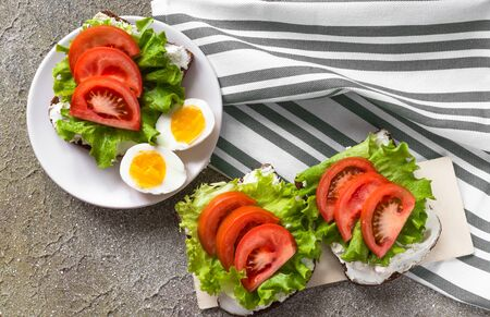 Healthy food for snack or lunch. Boiled cut eggs and sandwiches. Rye bread with cream cheese, tomatoes and lettuce on cement background and linen towel. Flat lay design. Home food