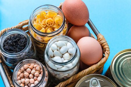 Donation box with eggs, pasta, kidney bean, chickpea and tea in glass jar and tin can on blue