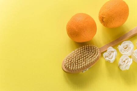 Body brush with big oranges and white soap in rose form for anti-cellulite massage on yellow background. Flat lay design with copy space. Cactus exfoliating brush for body care