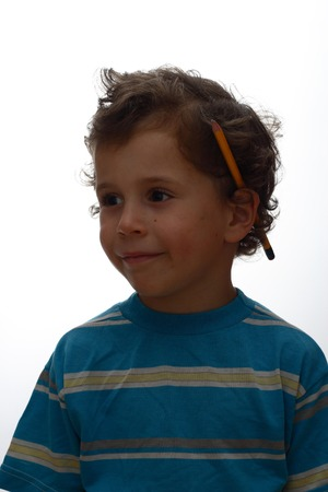 A smiling boy with yellow a pencil behind an ear on a white background photo