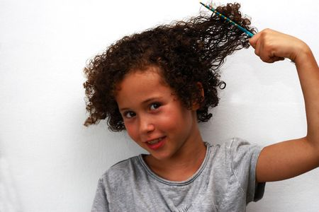 A smiling curly girl combs hair on a white background Stock Photo