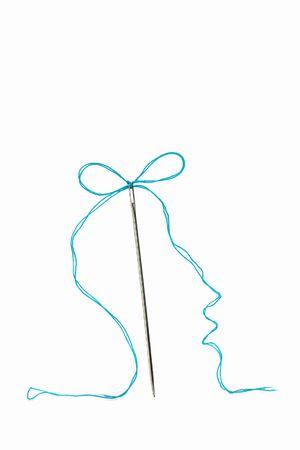 needle and turquoise thread bow on white background Stock Photo