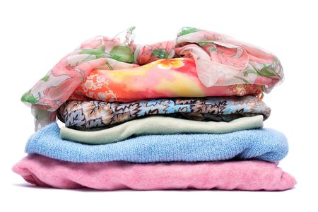 Stacks of women colored clothes on white background Stock Photo