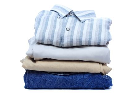 Stacks of manly colored clothes on white background