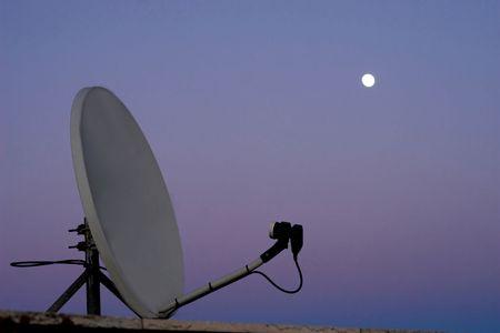 Satellite dish on sunset with moon.