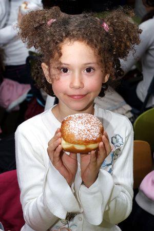 Smile girl with sufgania on Hanukkah