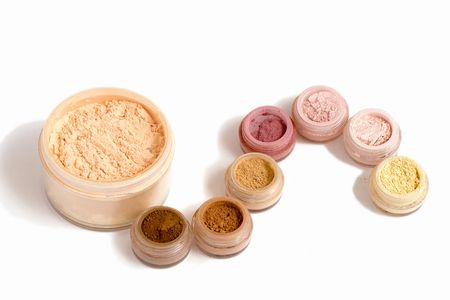 Set of multicolored powder and other cosmetics (isolated on white) Stock Photo