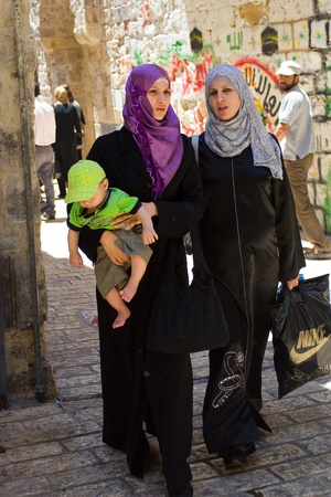 israel people: Old City, Jerusalem, Israel - July 17, 2009: Two Arab Women walking on traditional costume, one holding baby.