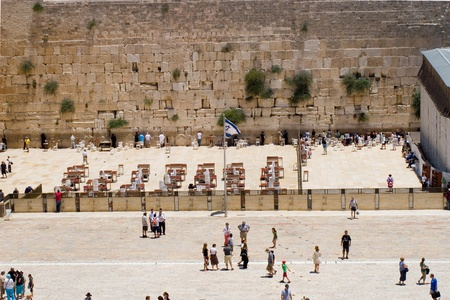 Western Wall, Jerusalem, Israel - July 17, 2009: People prays on male and female parts, people in area before, israels flag wave.