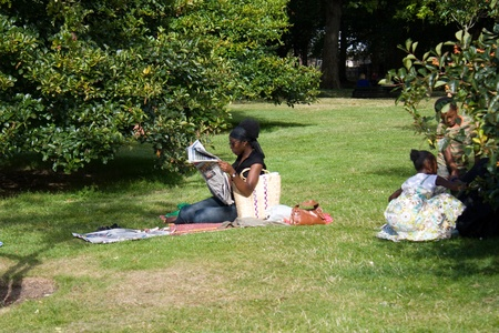 Green Park, London, United Kingdom - August 31, 2009. Afro family - mother and two children - are resting in park. Mother read newspaper, children playing near tree.