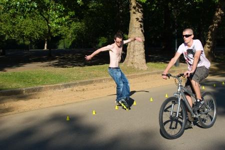 Hyde Park, London, United Kingdom - August 31, 2009. Roller (caucasian man) skating slalom and bicyclist.