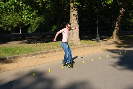 Hyde Park, London, United Kingdom - August 31, 2009. Roller (caucasian man) skating slalom.