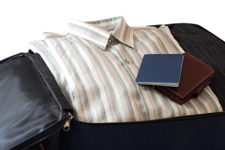 clothes, wallet and passport in suitcase (isolated on white background).