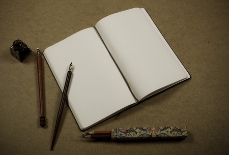 notebook on brown background with color pencils,  brushes and drawing tools with retro filter effect photo