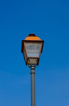 A street lamp with blue sky and clouds as background photo