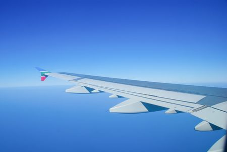THE WING OF AN AIR BUS PLANE ON A PERFECTLY BLUE SKE photo