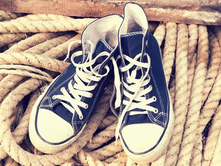 mare agitato: Un paio di vecchi stivali sporchi blu sport bianco su una corda mare agitato. stile Hipster. Retro tonica Archivio Fotografico