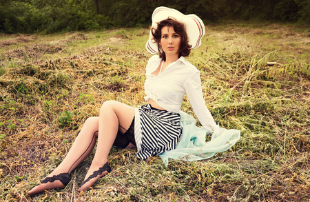 Cute sensual young woman in retro pin up style sitting on a field. Outdoor scenery. Vintage toning