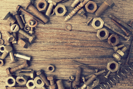 tuercas y tornillos: Foto de tuercas, pernos y tornillos sobre un fondo de madera en mal estado. retro tonificado Foto de archivo
