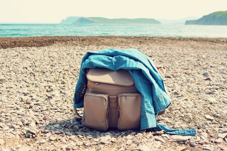 Travel hipster female backpack with jeans shirt  on a sea coast. Fashion vacation concept