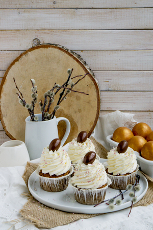 Carrot Easter cupcakr with chocolate egg on top and whipped cream frosting close up selective focus on wooden background and colored eggs