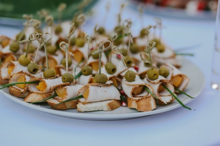 toothpick: Little sandwiches with ham and olives on a white plate