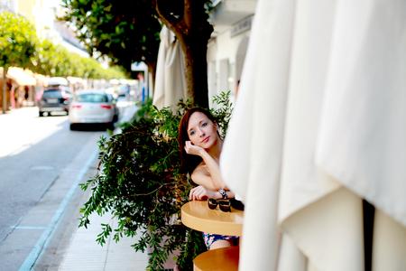pareja comiendo: La muchacha que se sienta en una mesa en la calle