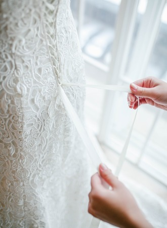Bridesmaid helps to put on a wedding dress