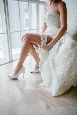 The bride wears wedding shoes. Wedding day