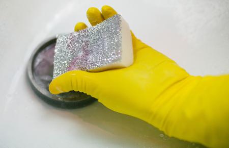hand in the yellow glove wash sink sponge