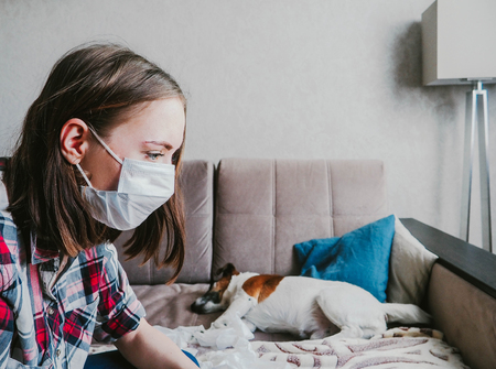 a young woman in a medical mask and petting a dog suffers from allergies at home