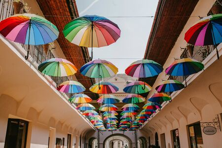Colorful umbrellas are suspended and decorate the street, art