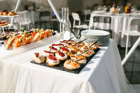 Assorted snacks on the buffet table. Sandwiches with fish, cheese and sun-dried tomato