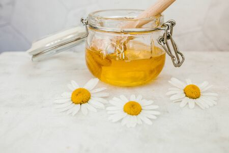 jar of honey with a wooden spoon for honey on a light background, sweet