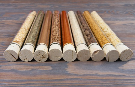 Glass tubes with spices and condiments on a wooden table background Stock Photo