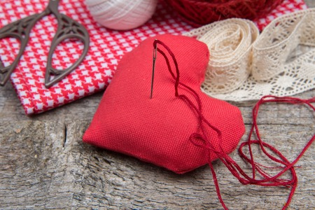 needle laces: Needlework background: red handmade heart with a needle and thread, lace and scissors on a wooden table