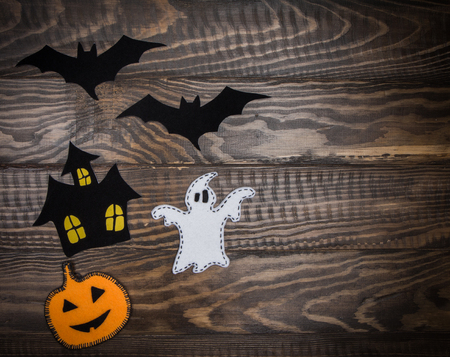 Bats, jack lantern, ghost and a haunted house on a dark wooden background. Halloween handmade