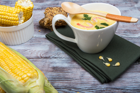 tureen: Corn soup with shrimps in a white tureen closeup with corn and bread on a wooden table