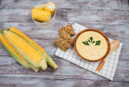 Corn soup in a wooden bowl on a white towel on a wooden background Stock Photo