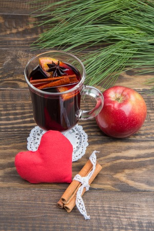 apple christmas: A glass of hot mulled wine, heart and a red apple. Christmas drink