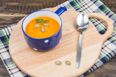 tureen: Homemade pumpkin soup in a blue tureen and a metal spoon on a wooden cutting board. Dark wood background. Autumn Stock Photo
